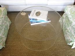 round clear acrylic coffee table between white patterned fabric sofa in the shape of on brown rug flooring