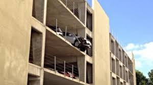 car dangles from garage s fourth floor after woman hits gas pedal