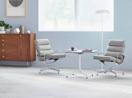 a round eames table with a white top paired with two light gray eames soft