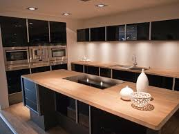 stove island. this sleek, high contrast modern kitchen features glossy black cabinetry juxtaposed against light natural wood stove island r