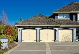 wood garage door styles. This Blue Brick Home Features An Attached Three Car Garage With Light Yellow Painted Wood Carriage Door Styles