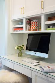 chic work space is filled with a built in desk ed with a glass top lined with an acrylic chair dd in a sheepskin pelt placed under overhead cabinets
