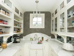 u shaped kitchen pantry boasts a mini george ii chandelier illuminating a farmhouse sink and nickel deck mount faucet finished with a white curved marble