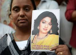 a woman holds a picture of late bollywood actress sridevi kapoor as she stands outside her