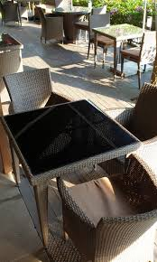 brown rattan table with black glass top