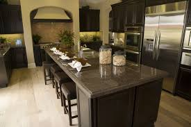 Dark Kitchen Design With An Extra Long Island That Contains A Long Dining  Bar As Well