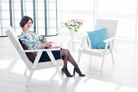 expert psychologist practitioner in a bright office beautiful modern space with an armchair for the client business suit spring mood everyday makeup beautiful bright office