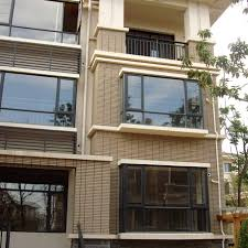 modern indian houses with cream exterior wall tiles design and some glass window with black wood