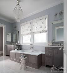 gray wainscoted bathtub under clear beaded chandelier