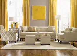 dove grey wall contrasts with sunny yellow curtains and an artwork the room is infused