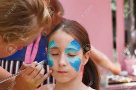 child animator artist s hand draws face painting to little girl child with funny face