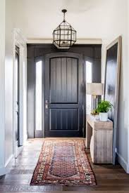 Stunning Hamadan runner rug and black door entrance by The white walls and  wood furniture makes for a great boho style!