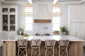 stunning center island in a cottage kitchen boasting brown brushed oak with macaubas quartzite countertops fitted with brown wicker stools