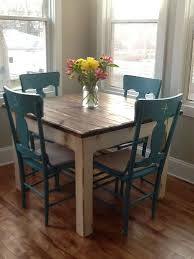 quaint square table with wood finish top offset with white distress and finished with the dark turquoise chairs perfect for a little cote kitchen