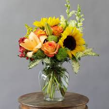 beautiful sunflowers roses lilies snapdragons and assorted seasonal flowers arranged in a