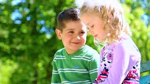 boy is looking at beautiful closeup portrait cute couple in love happy smiling children outdoors green nature close up of beautiful kids