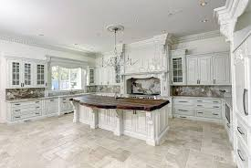 traditional kitchen with white cabinets honed travertine floors and wood counter island with large chandelier