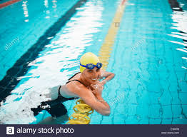 portrait of smiling swimmer leaning on swimming lane marker in pool stock image