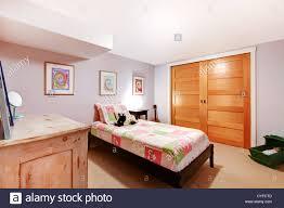 PInk girl kids bedroom in the basement with closet doors and dresser