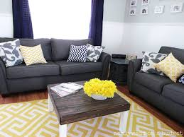 Yellow And Grey Living Room. White walls. Bright yellow plant on deep  coffee table