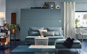 A medium sized living room furnished with a turquoise three-seat sofa and a  footstool