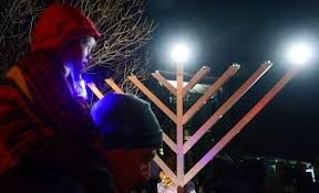 a child on his father 8217 s shoulders on the first night of hanukkah