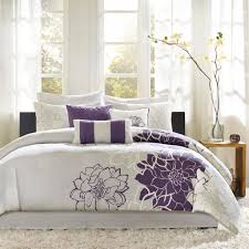 a bedding set with purple flower motif and less gray decorative motifs white fluffy area rug