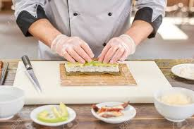 Sushi Cook Chef Preparing Sushi With Eel And Avocado Chef Hands In Disposable