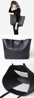 this large black leather tote has small feet on the bottom so you don t have to worry about setting it down on the floor