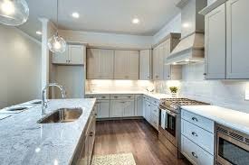 snowfall granite countertops transitional kitchen with gray cabinets arctic white quartz snowfall granite subway tile snowfall