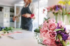 beautiful flower bouquet in garden center with woman florist working in background focus on fresh flower bouquet
