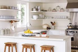 beautiful kitchen features stacked wraparound floating shelves filled with dinnerware and glass cloches with trays standing next to s stainless steel viking