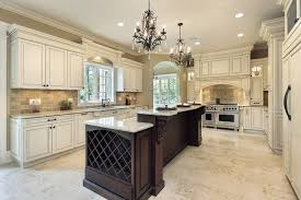 white luxury kitchen with granite island and two chandeliers