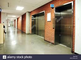 school bathroom door. Freight And Regular Steel Door Elevators With Signs In An Empty Hallway Of Modern Building. School Bathroom