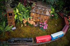 a model train passes in front of replicas of the van cortlandt house and the riverdale