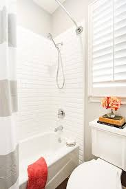 kids shower with white beveled subway tiles and gray striped shower curtain