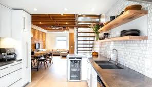 modern basement kitchen exposed wooden beams brick wall dining and living area open shelving shelves dusty