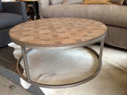 round light brown wooden coffee table with silver steel frame also base placed on the white