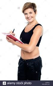 Female Gym Instructor Writing Diet Chart For Trainees All