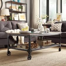 This modern coffee table features wheels, a weathered top and sturdy metal  base with shelf