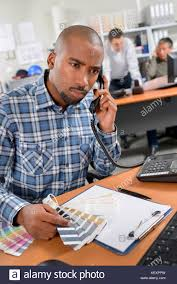 Man On Telephone Holding Colour Charts Looking Confused