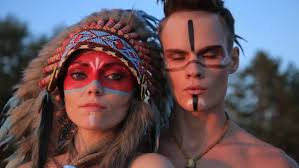 beautiful native american indian man and woman in traditional dress at the sea beach sunset