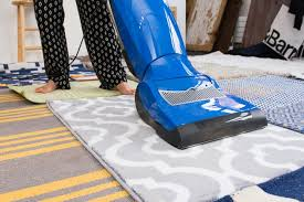 a person using a blue vacuum cleaner on several rugs dotted with small debris