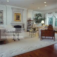 living room sculptured border of rug in corner of traditional room with mahogany furniture off white rug looking to fireplace gold framed artwork over