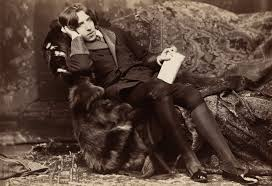 oscar wilde  a tall man rests on a chaise longue facing the camera on his knees oscar wilde