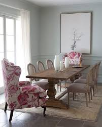 a vintage rustic dining room is spruced up with pink fl upholstery wingback chairs