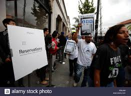 protesters against the low wages of service workers on tech protesters against the low wages of service workers on tech campuses outside the apple store in pasadena california past a line of people waiting to