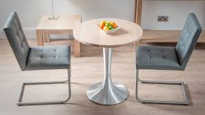 round light oak dining table with grey cantilever dining chairs