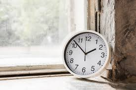 close up of small white round clock near the glass window free photo