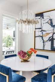 brass and lucite chandelier over round white dining table